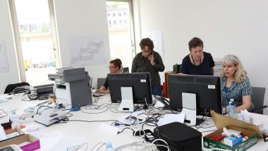 Mai multe persoane lucrează într-un birou.