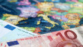 Euro banknotes on the map of Europe, selective focus. Concept for european economy, eurozone countries