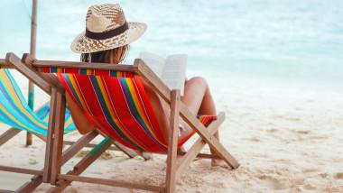 fata cu palarie si carte in mana pe sezlong la plaja