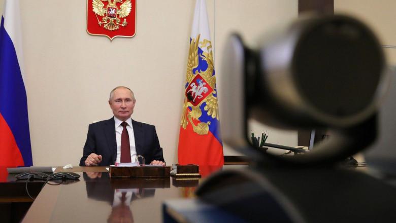 Președintele rus Vladimir Putin sta la birou in fata unei camere de luat vederi