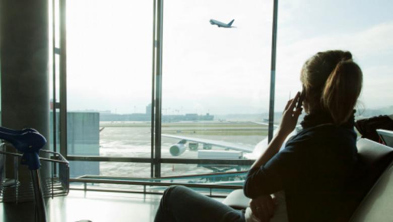 femeie care vorbeste la telefon in aeroport