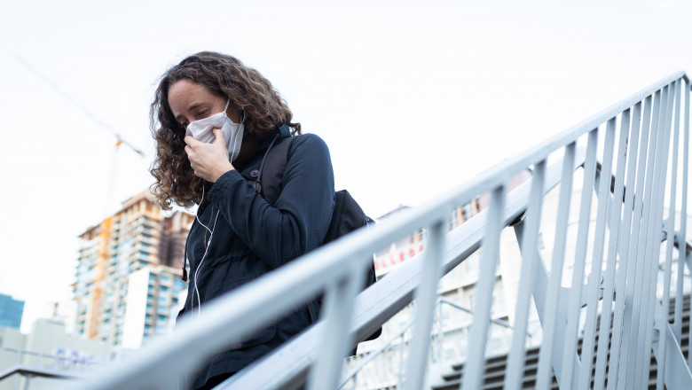 Caucasian woman out and about in the city streets during the day, wearing a face mask against covid19 coronavirus, walking down stairs on a pedestrain bridge and covering her face while coughing