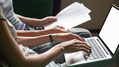 Couple holding reading documents at home with laptop, close up