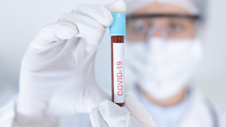 Caucasian female healthcare worker wearing a lab coat, face mask and surgical gloves against coronavirus, covid 19, holding an ampoule with blood sample.