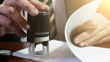 un functionar publoc pune o stampila pe un document