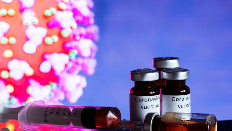 doze de vaccin si o siringă în prim plan, ilustrație a virusului covid în fundal