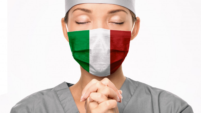 Italy flag print on surgical mask. Doctor praying for help. Young Asian woman medical doctor praying for Italy. Coronavirus pandemic outbreak in Italy