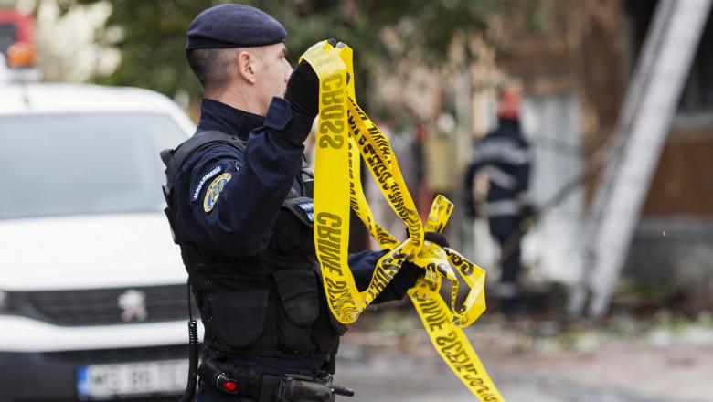 un jandarm care întinde o bandă pentru delimitarea locului unei crime