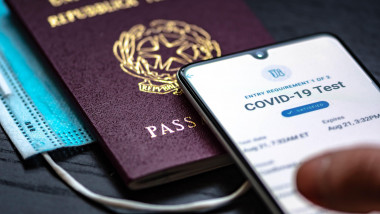 Vaccine passport app displayed an a smartphone with passport and mask, Covid-19 immunity passport