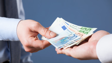 Businessman's hands exchanging euro on blue background