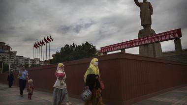 Femei uigure trec prin dreptul statuii lui Mao, într-un oraș din regiunea Xinjiang, China