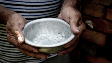 The poor old man's hands hold an empty bowl. The concept of hunger or poverty. Selective focus. Poverty in retirement. Homeless. Alms