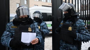 politisti rusi de la trupele speciale, cu echipament de protectie si casc, verifica o lista cu invitati