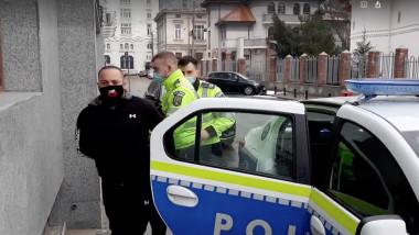 barbat cu mainile legate coborat de politisti din masina si retinut