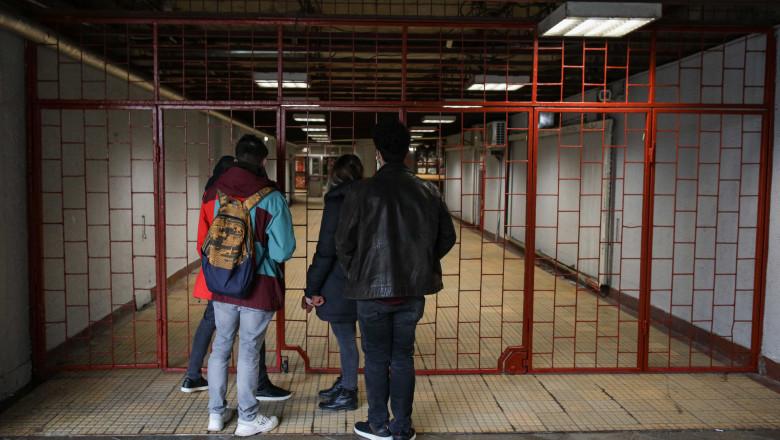 tineri stau in fata unei porti incuiate la metrou.