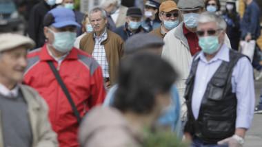 Oameni cu mască pe stradă.