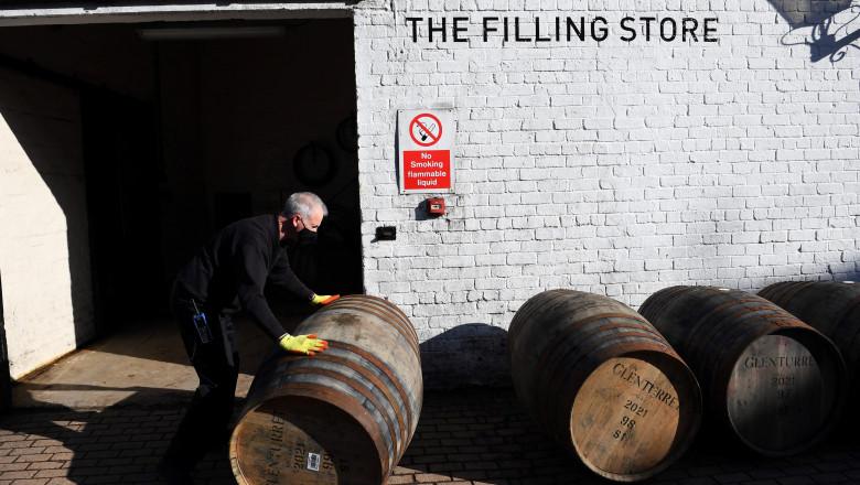Butoaie cu whisky în faţa celei mai vechi distilerii de whisky din Scoţia