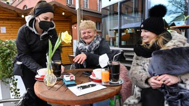 persoane care stau la masa intr-un oras din germania