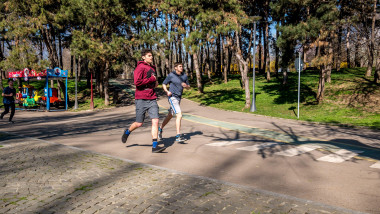 Tineri aleargă într-un parc din Bucureşti