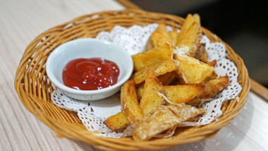 A wooden basket of potato wedge fries with tomato ketchup
