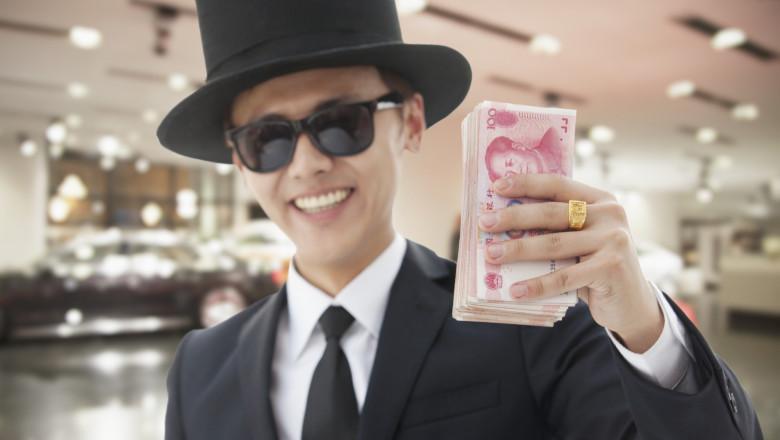 barbat din china arătând un teanc de bani