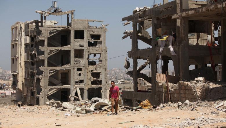 Palestinieni în faţa unor clădiri distruse în Gaza, după atacurile armatei israeliene din 2014.