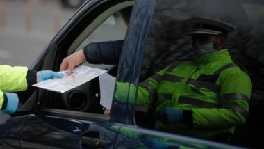 Un șofer prezintă actele polițistului după oprirea la un filtru in localitate carantinată.