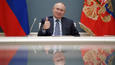Vladimir Putin face semnul OK în timp ce stă la biroul prezidențial