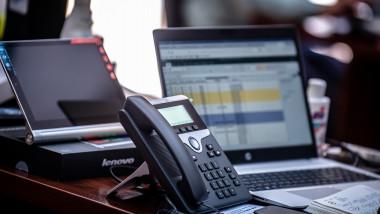 Telefon și monitor pe un birou.