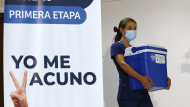 """un cadru medical cara o ladă frigorifica cu vaccinuri trecand pe langa un panou pe care scrie in spaniola """"eu ma vaccinez"""""""