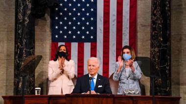 Joe Biden pe podium, ]n spate sunt vicepreședinta Kamala Harris și lidera Camerei Reprezentanților Nancy Pelosi, cu steagul SUA pe perete
