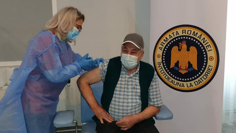 un batran cu masca este vaccinat intr-un spital militar