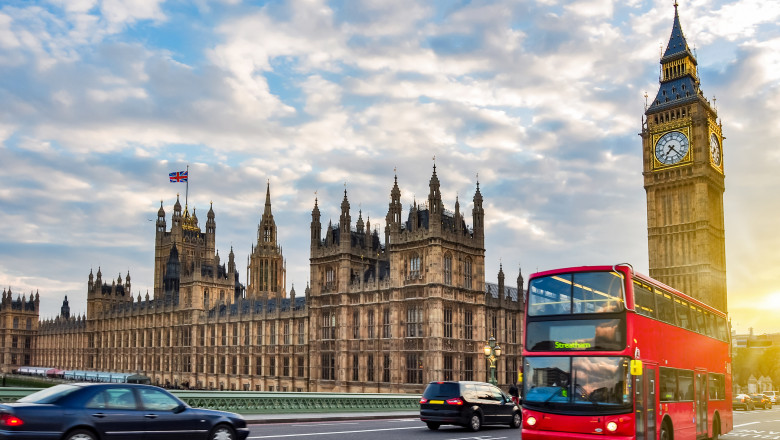 Houses of Parliament with Big Ben and double-decker bus on Westminster bridge at sunset, London, UK