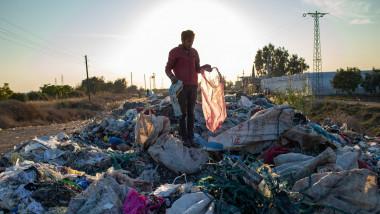 un om cauzta prin gunoaie de plastic aruncate pe camp