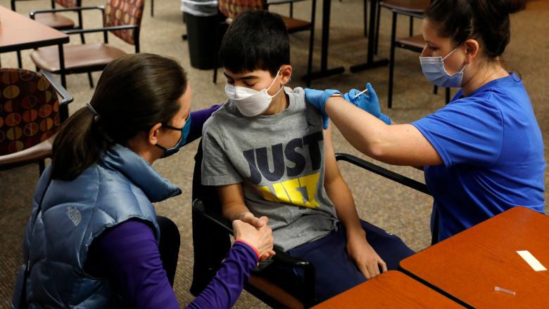 un copil este tinut de mana de o femeie in timp ce este vaccinat anti covid