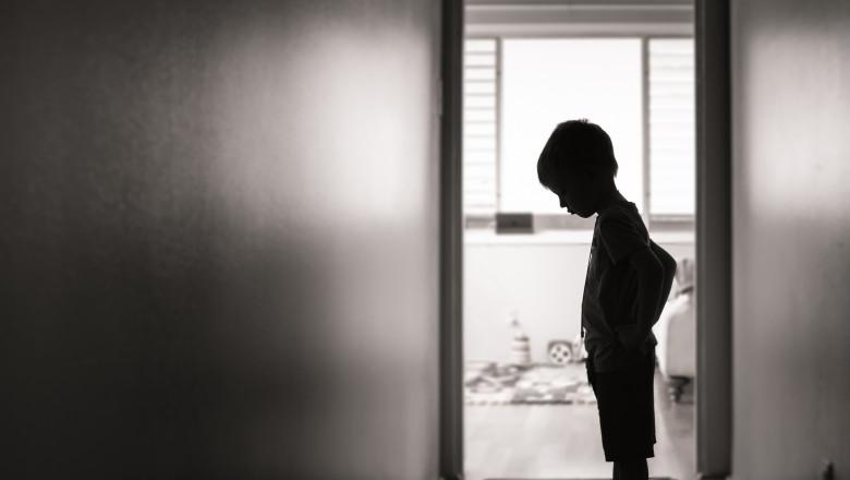 Sad boy standing alone in the hallway