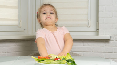 a little girl sits at a table in the kitchen and pushes away a plate of vegetables. preschoolers do not want to eat vegetables