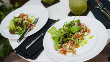 Two plates of fresh salad with arugula, mozzarella, vegetables, tomatoes, chicken served mint lemonade in a small outdoor restaurant at the lunch