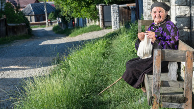 An elderly woman doing crochet on a bench on the road to Oncesti, Maramures region, Romania
