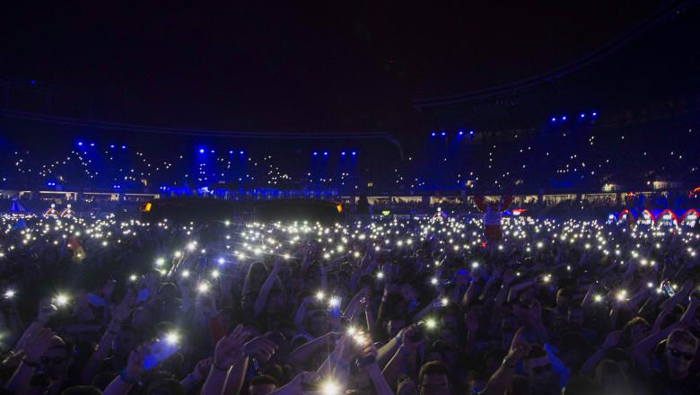 participanti la untold cu luminite aprinse la telefoane