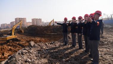 nord coreeni cu casca pe cap si microfon cante pe santier despre constructia de locuinte