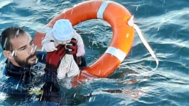bebelus tinut deasupra apei de un salvator spaniol, care se ajuta de un colac de salvare