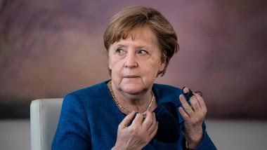 Angela Merkel își pune masca de protecție