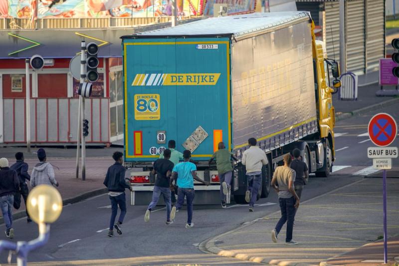 Migranți ilegali aleargă spre un TIR în încercarea de a trece din Franța în UK.
