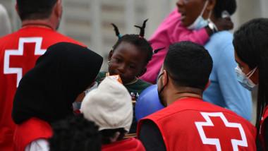 copil negru inconjurat de membrii ai crucii rosii