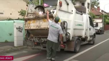 un angajat al romprest arunca gunoi in masina de salubritate