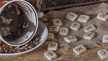 Isoteric concept of divination and prediction. Tarot cards, runes, coffee grounds in a cup, rosary on a table against the background of an old chest