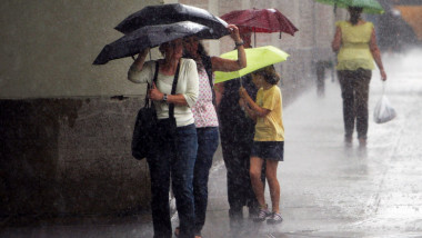 persoane sub umbrele pe strada in ploaie