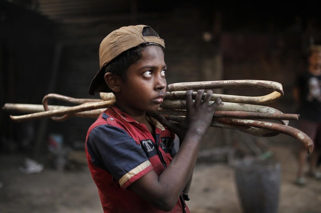 Copil din Bangladesh care cară pe umeri bețe din fier