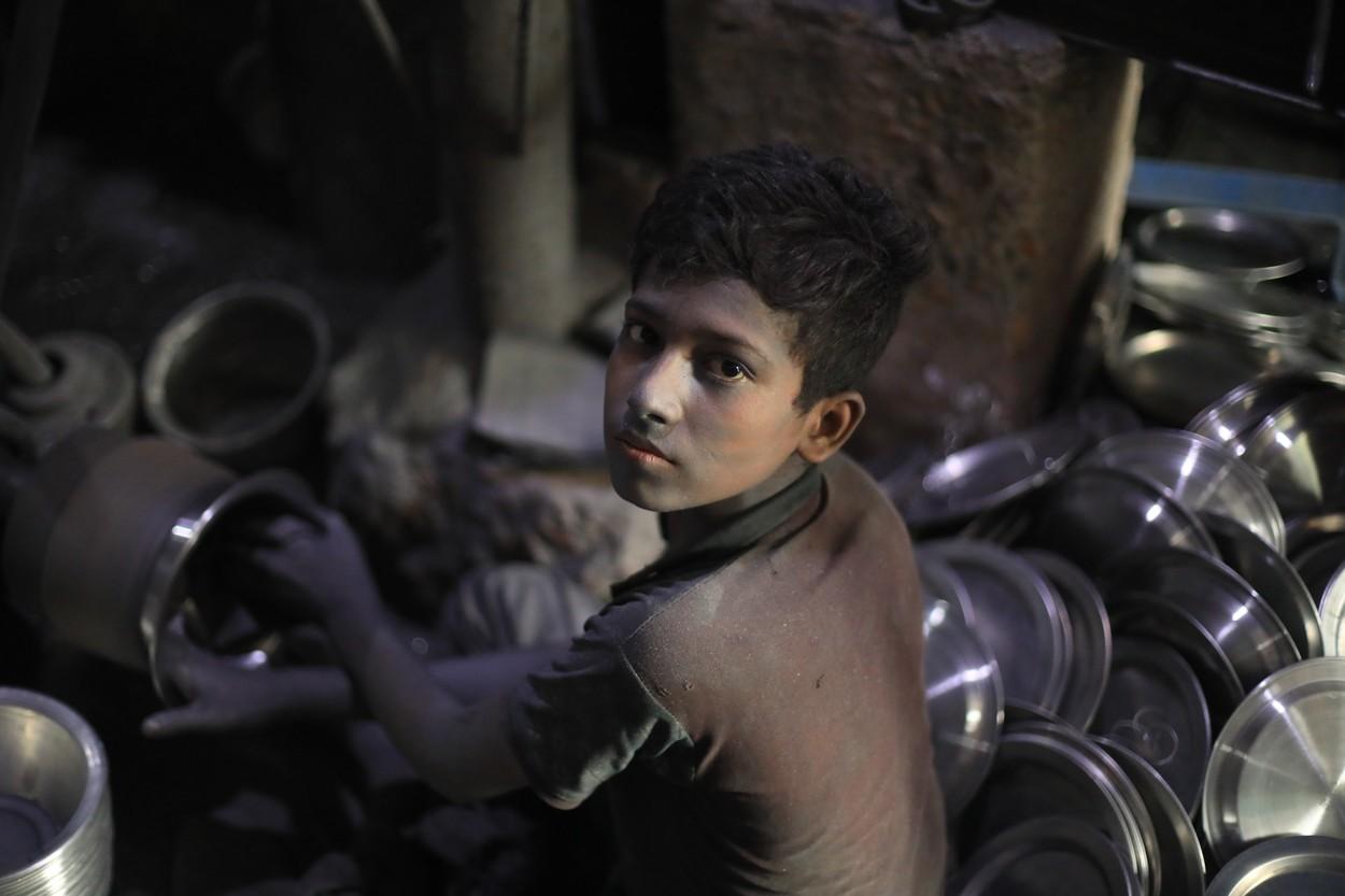 Copil de 13 ani din Bangladesh care lucrează la o fabrică de aluminiu.